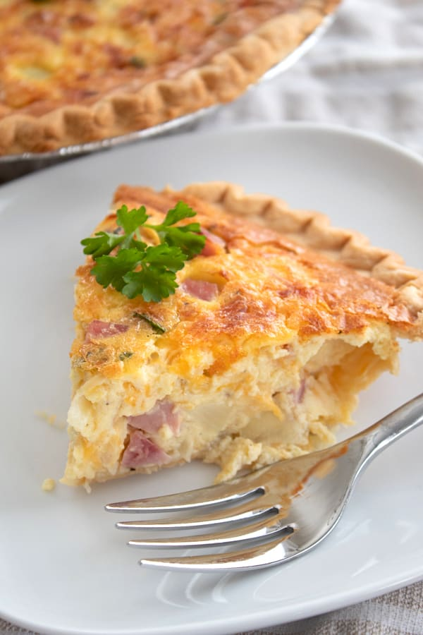 a slice of quiche on a white plate with a fork and parsley garnish
