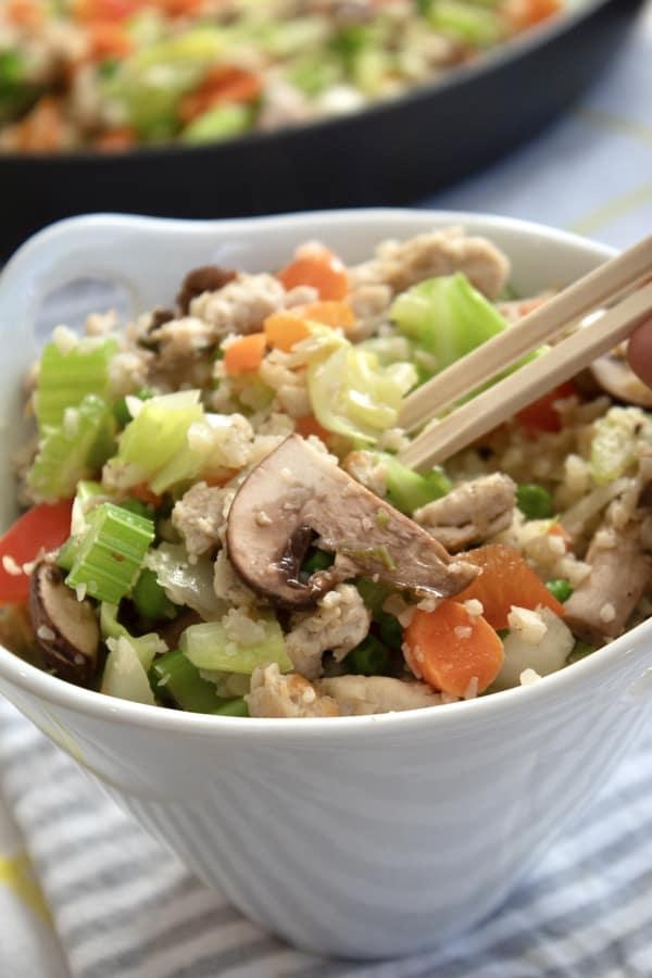cauliflower rice in a bowl with chopsticks