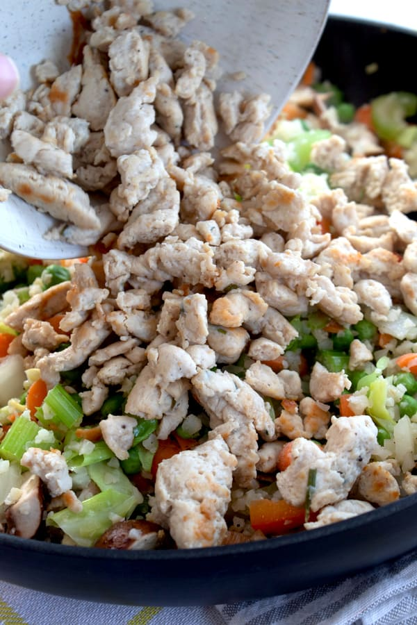 adding ground chicken to cauliflower rice stir fry