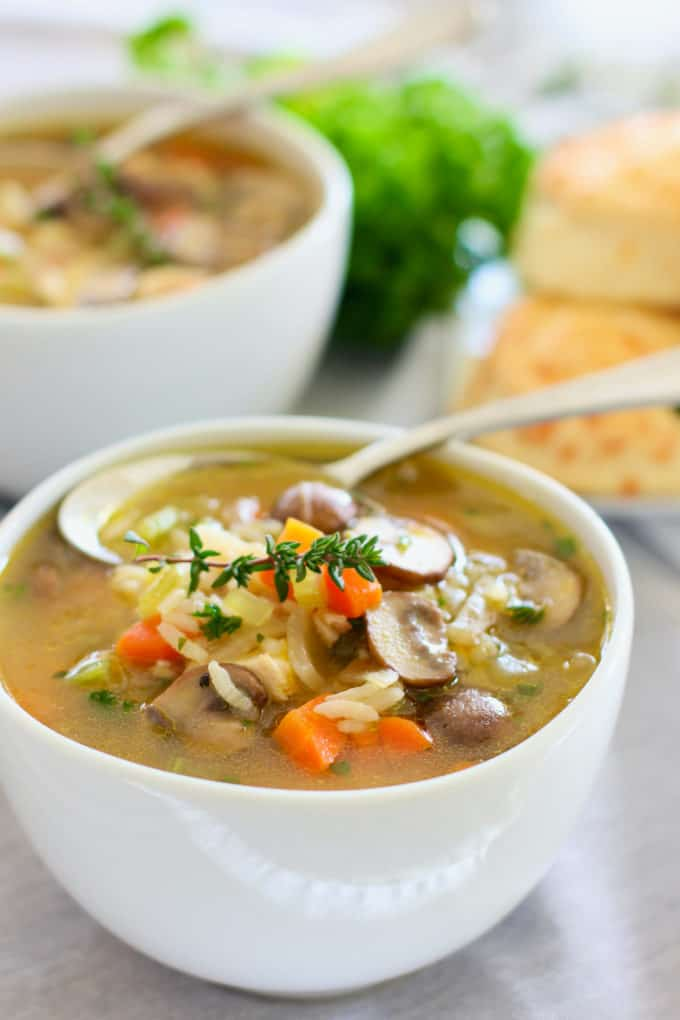 chicken and mushroom soup in a white bowl with spoon