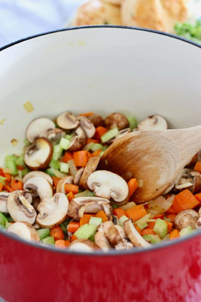 carrots onion celery and mushrooms in big red pot