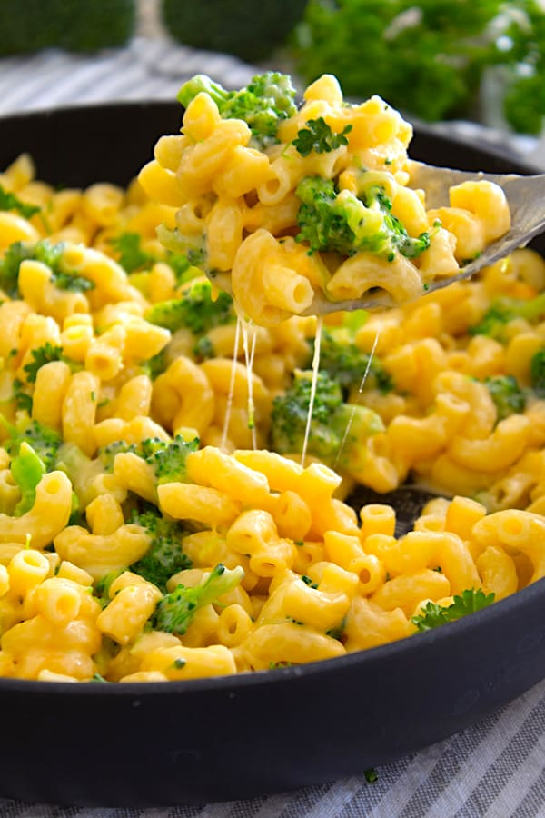 cheese pull of broccoli cheddar Mac and cheese in pan