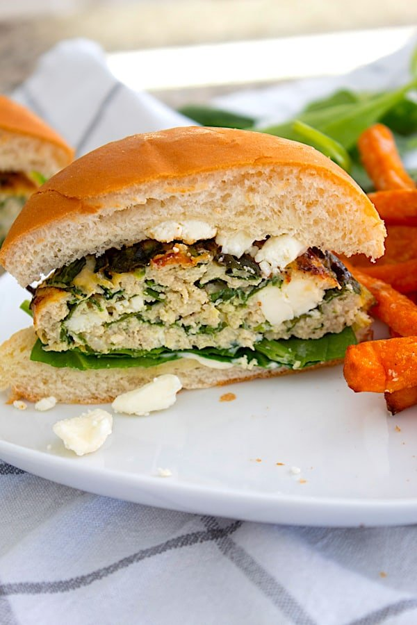 spinach feta burger cut in half with sweet potato French fries