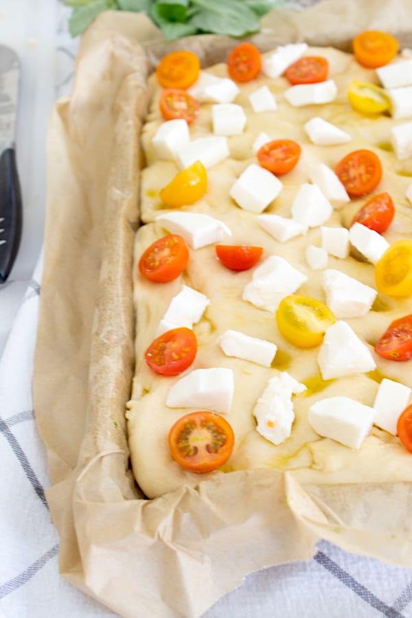 adding mozzarella tomatoes and basil to top of focaccia bread