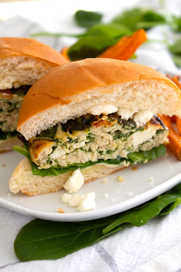 spinach feta burger in half on plate with sweet potato fries