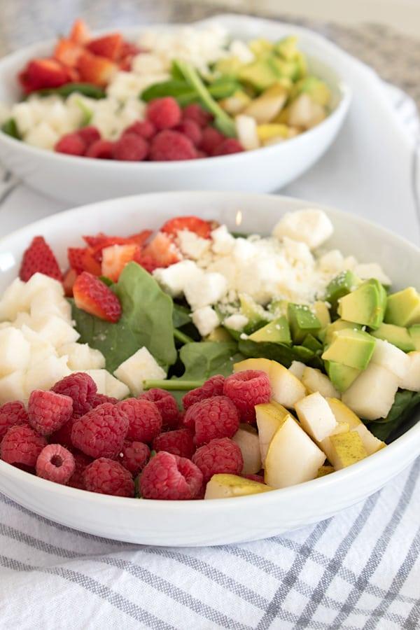 adding ingredients to salad in white bowl