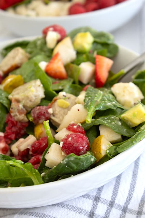 salad in white bowl with poppyseed dressing and avocado