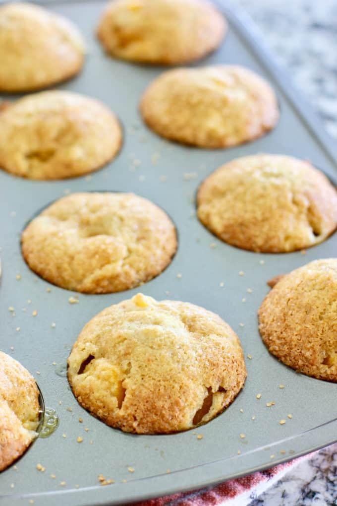 peach cobbler muffins in a muffin tin