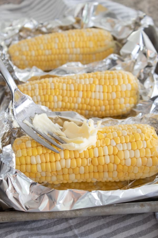 adding butter to raw corn
