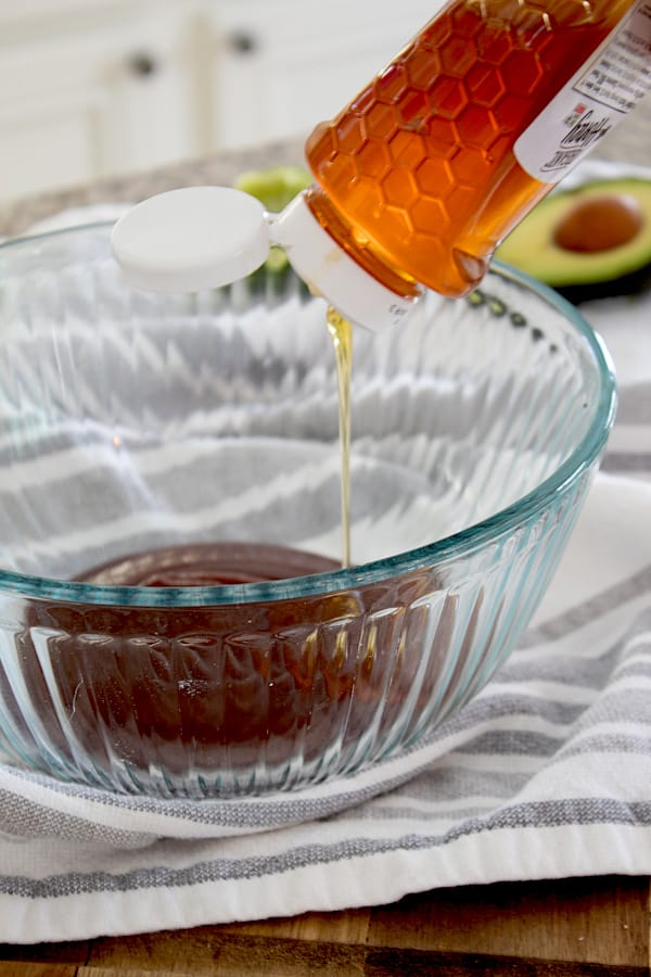 mixing bbq sauce with honey in clear glass bowl