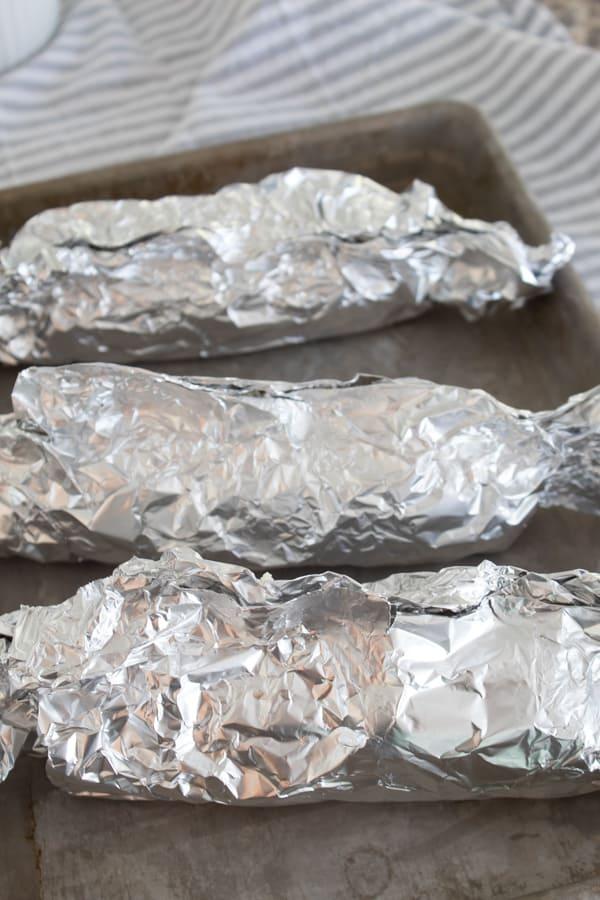 wrapped ears of corn in foil on a sheet pan