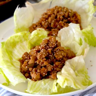 lettuce wraps with chicken filling on a white plate