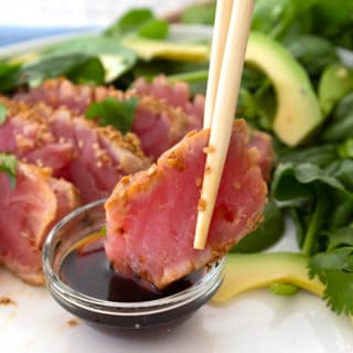 holding piece of seared ahi tuna being dipped in soy sauce with chopsticks