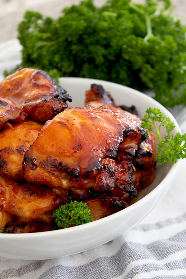 bbq chicken in a white dish with parsley garnish