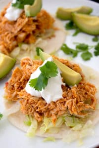 tortilla with shredded lettuce, taco meat, sour cream, avocado and cilantro garnish on a white platter