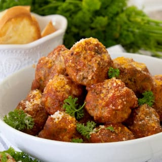 meatballs on a white bowl platter with parsley and crostini in background