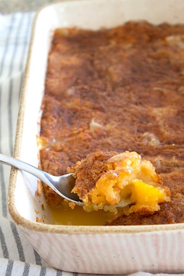 peach dump cake in a casserole dish being spooned