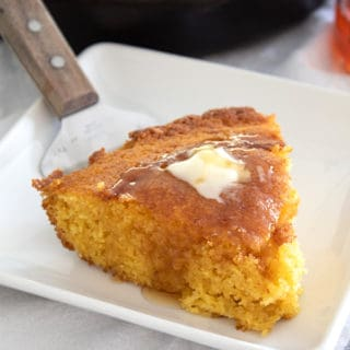 white plate with slice of skillet cornbread with honey and butter on top