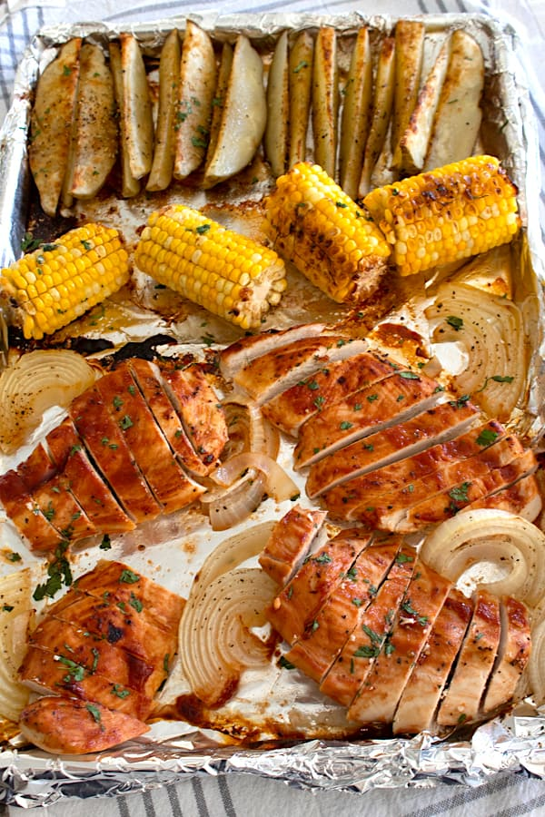 overhead view of sheet pan chicken dinner with corn and potato wedges