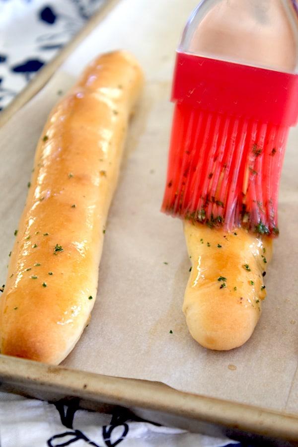 brushing breadstick with butter using basting brush