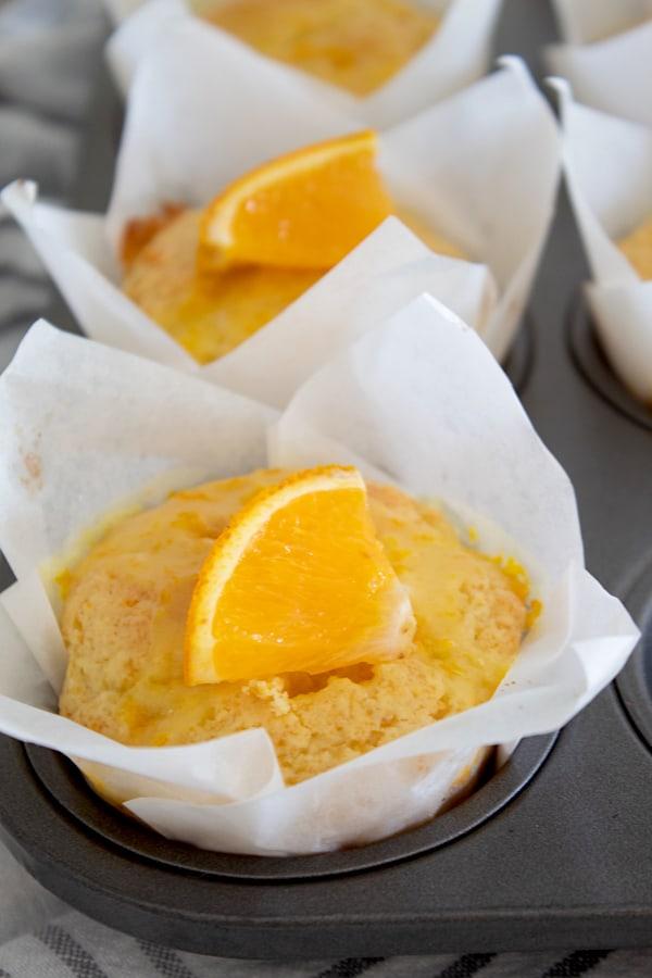 orange muffins garnished with an orange slice