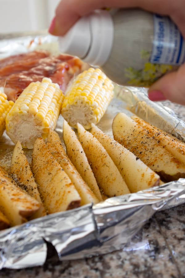 potatoes chicken and corn being sprayed with nonstick spray
