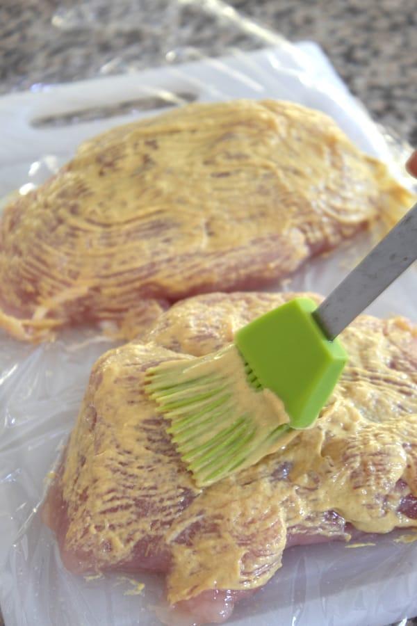 brushing turkey breast with dijon mixture