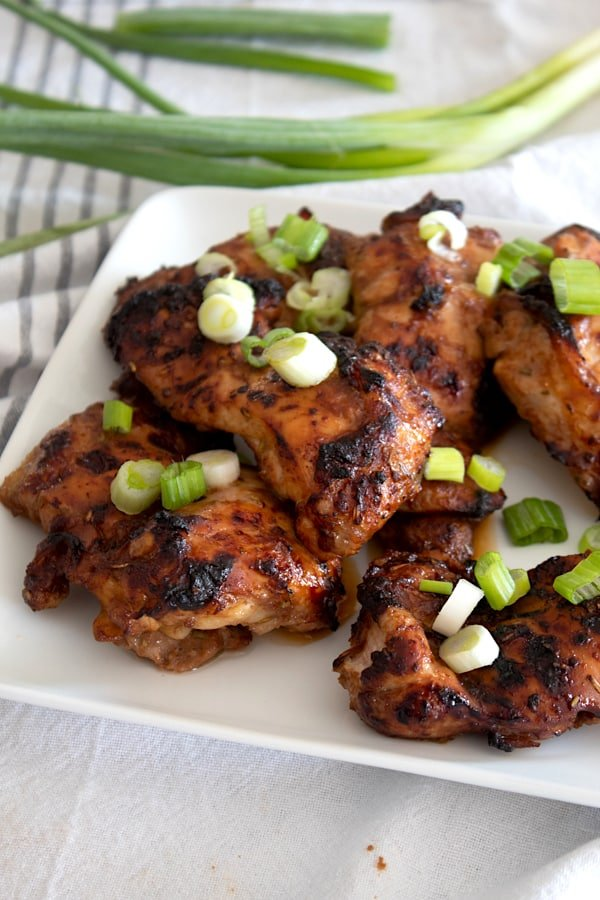 marinated chicken thighs on a plate garnished with green onion