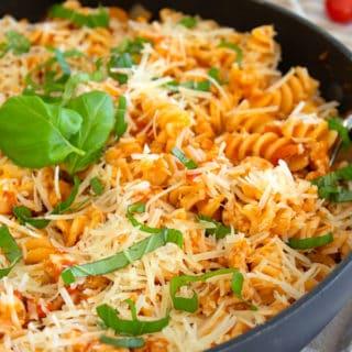 ground chicken pasta skillet in a black pan garnished with basil